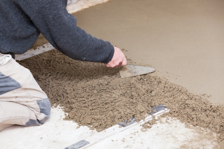mason leveling the cement screed photo