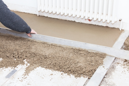 mason leveling the cement screed Standard-Bild