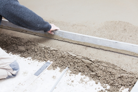 mason leveling the cement screed Stock Photo