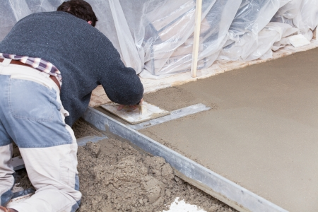 mason smooth the cement screed with trowel photo