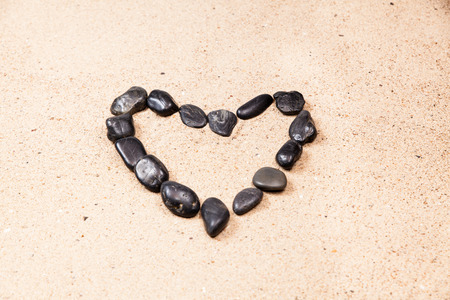 heart drawn with pebbles on the beach sand photo