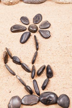dessin fleur: dessin avec des cailloux sur le sable d'une plage de fleur Banque d'images