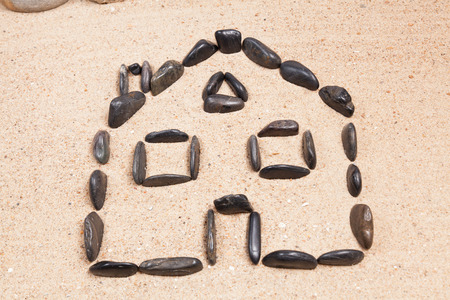home designed with pebbles on the sand of a beach photo