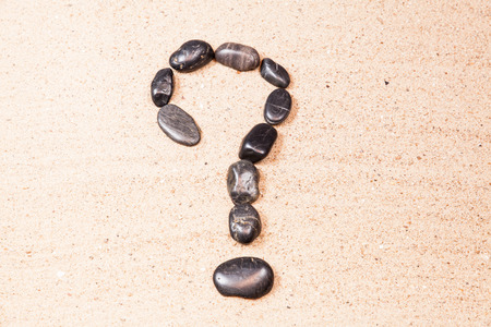question mark drawn with pebbles on the sand of a beach photo