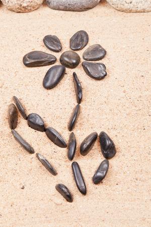 dessin fleur: dessin avec des cailloux sur le sable d'une plage fleur