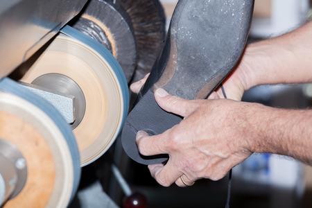 the shoemaker repairs a shoe photo