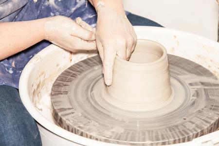 alfarero: Mujer Potter creando una vasija de barro en un torno de alfarero Foto de archivo