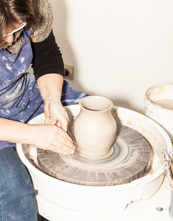 potters wheel: Female Potter creating a earthen jar on a Potters wheel