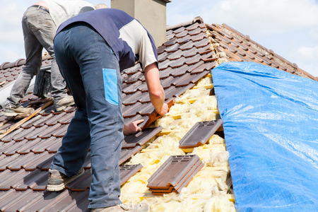 Un roofer posa di piastrelle sul tetto Archivio Fotografico - 40105373