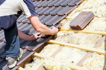 roof structure: a roofer laying tile on the roof
