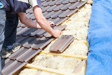 remodeling: a roofer laying tile on the roof