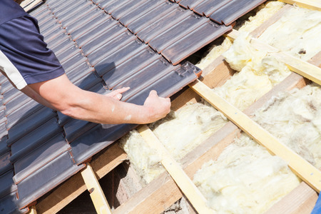 roofer: a roofer laying tile on the roof