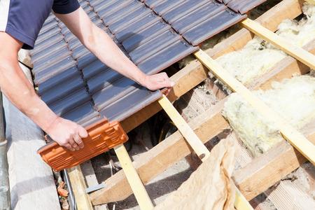 Un couvreur pose de carrelage sur le toit Banque d'images - 40186691