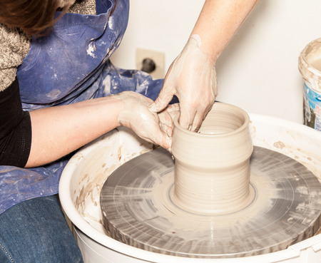 creating: Female Potter creating a earthen jar on a Potters wheel