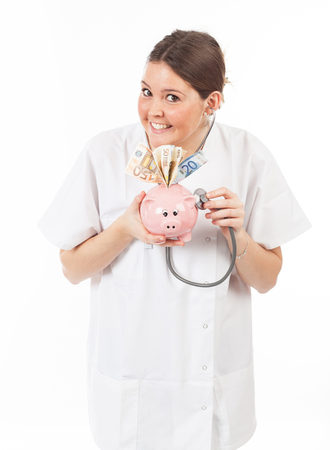 doctor money: happy woman doctor with piggy bank full of money Stock Photo
