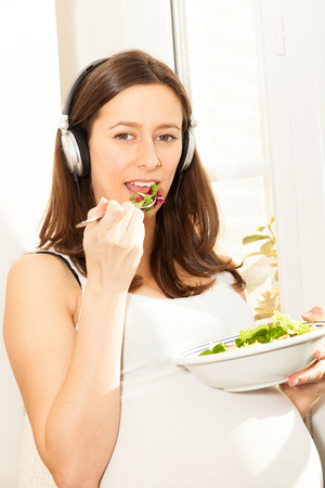 tummy time: pregnant woman eat salad and listening to music