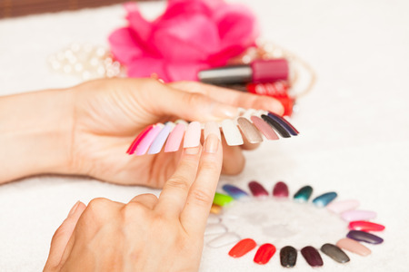 nails: Hands of a woman who chooses the color of her nail polish