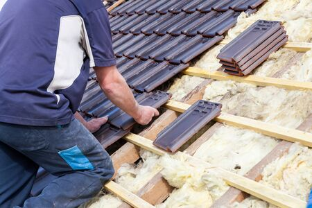 a roofer laying tile on the roof Stock Photo