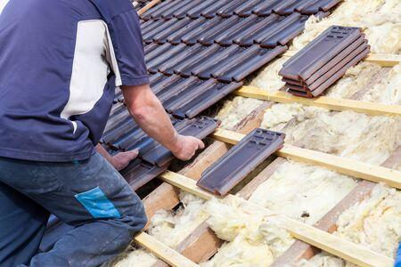 ein Dachdecker, der Ziegel auf das Dach legt Standard-Bild
