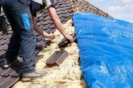 ein Dachdecker, der Ziegel auf das Dach legt