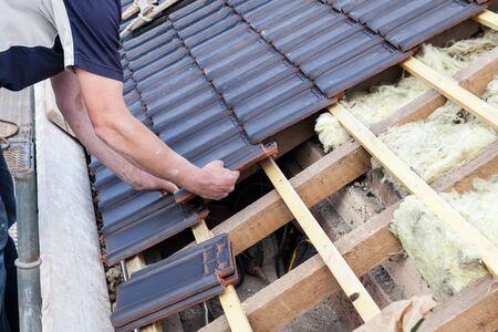 een dakdekker die tegel op het dak legt Stockfoto
