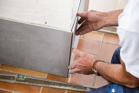the tiler lays a ceramic tile on the wall Zdjęcie Seryjne