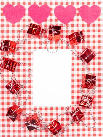 background with red and white Vichy fabric for Valentine's day with pink hearts, small gifts, garlands of small pearls and a white card to put the text. valentines day concept