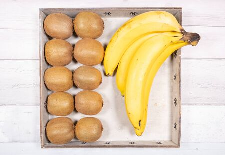Bananas and kiwis placed in an old wooden tray on a background of old wooden floor.