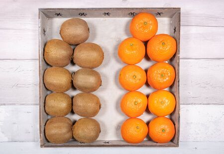 Mandarins, clementines and kiwis placed in an old wooden tray on a background of old wooden floor. Stock Photo