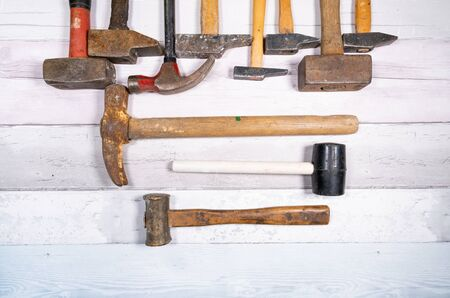 set of different types of old hammers on a wooden background. top view.