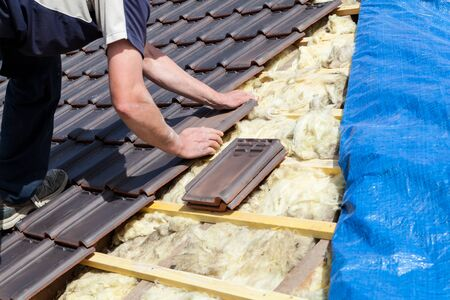 a roofer laying tile on the roof Stockfoto