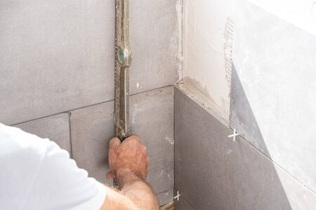 the tiler lays a ceramic tile on the wall Stockfoto