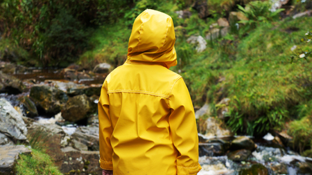 Child in Yellow Rain Coat watches the River