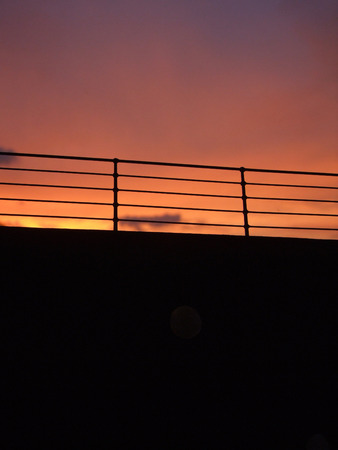 Silhouette of a Cruise Ship Railing against a Sunset Sky