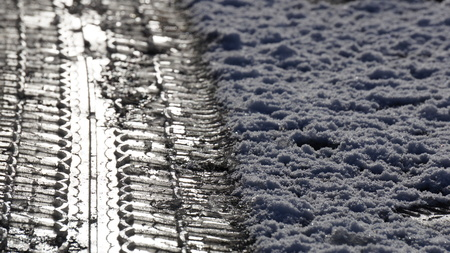 Snow sleet ice covered road with tyre tread impressions