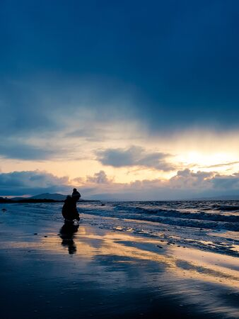 Silhouette of a child crouching at the edge of the sea