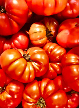 several big tomatoes creating a red and textured background