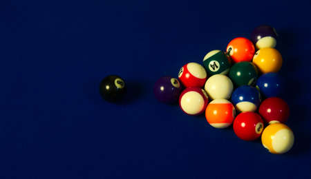 Billiard black ball moving close to a group of colored balls 写真素材