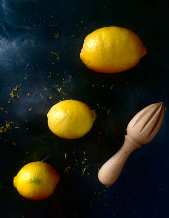 Three lemons of different sizes over black table and wood squeezer at the right side Stock Photo