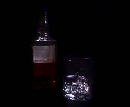 Straight on picture of bottle of whiskey and glass including ice cubes