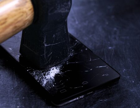 45 degrees close up picture of black mobile phone screen broken by black hammer, all over black board