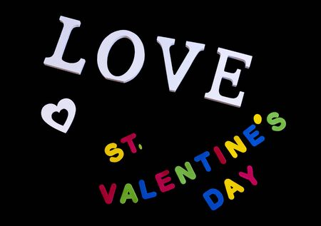 Overhead picture of white word love, white heart and colored word valentine's day, in black background Imagens