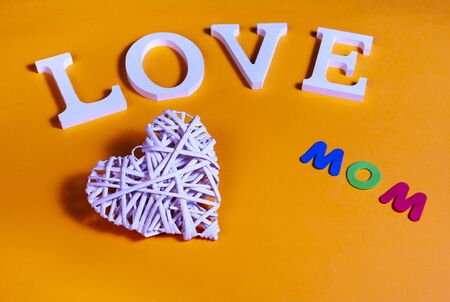 75 degrees picture of white word love, white heart in relief and colored word mom, in orange background Imagens