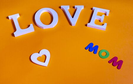 75 degrees picture of white word love, white heart and colored word mom, in orange background