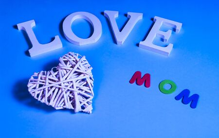 75 degrees picture of white word love, white heart in relief and colored word mom, in blue background Imagens