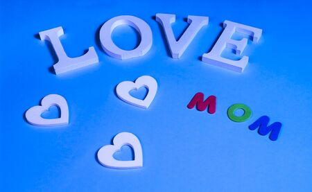 75 degrees picture of white word love, three white hearts and colored word mom, in blue background
