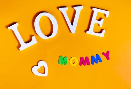 Overhead picture of white word love, white heart and colored word mommy, in orange background Imagens