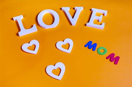 75 degrees picture of white word love, three white hearts and colored word mom, in orange background Banco de Imagens