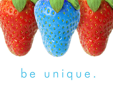 one of a kind: Blue strawberry between red ones. Stock Photo