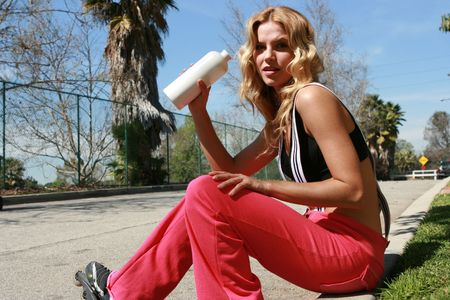 roller blade: A pretty girl drinks water after roller blading